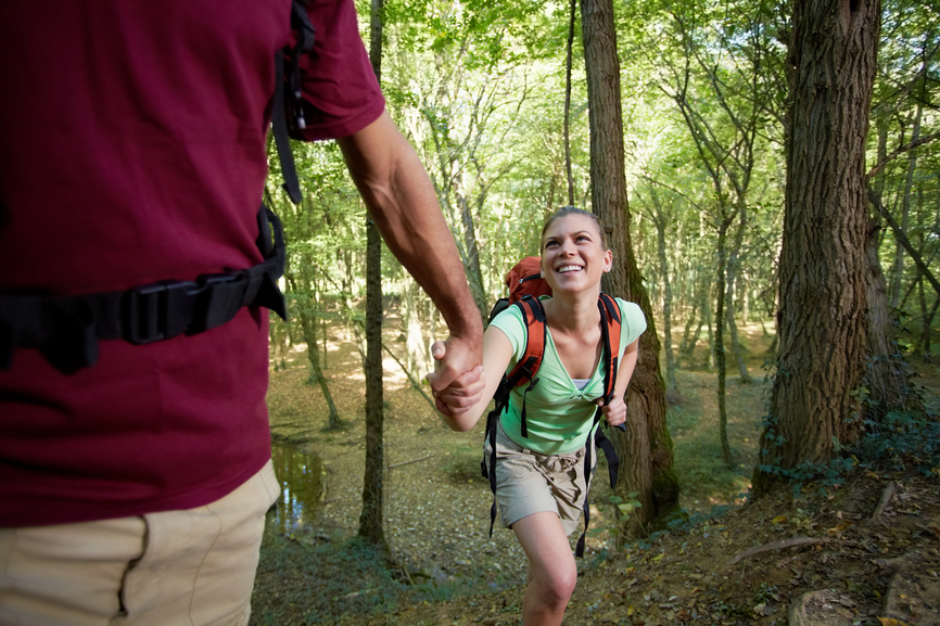 young couple trekking in forest and holding hands