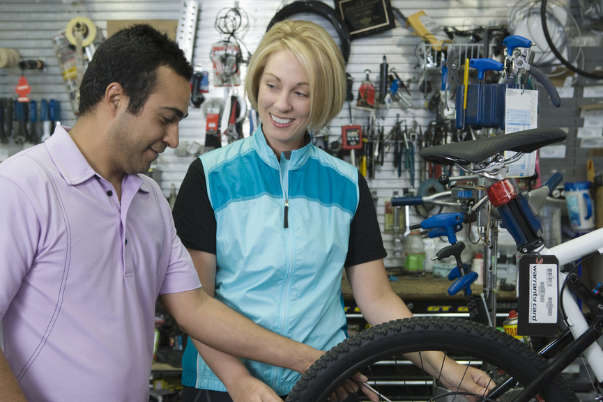 Shop Keeper Assisting Female Cyclist In Store